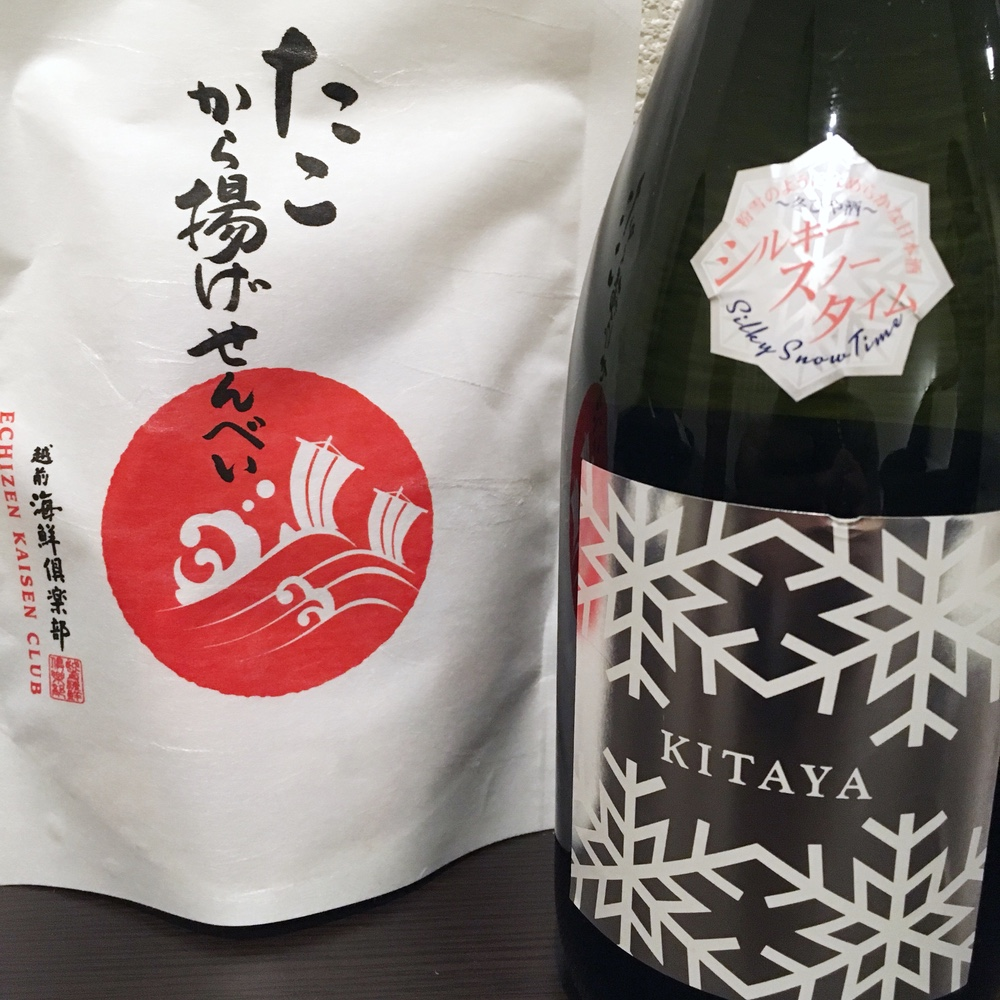 フルーティな甘さが特徴的な日本酒「シルキースノータイム喜多屋」と香ばしい「たこから揚げせんべい」